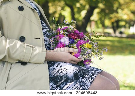 Closeup of pregnant woman in a light raincoat holding a bouquet of wildflowers in an autumn park outdoors new life concept
