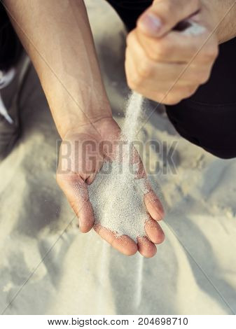 Sand flowing through your fingers. Hand with the sand.