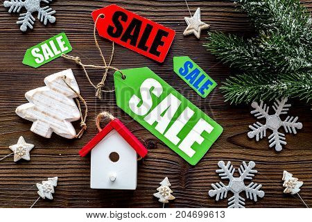 Christmas sale. Sale labels near spruce branch and xmas toys on wooden background top view.