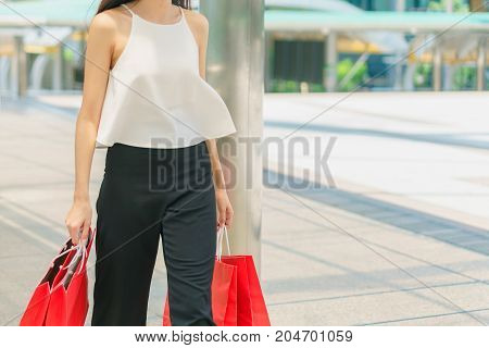 business and modern lifestyle concept: Beautiful young woman holding a big red bag with hands and walking on the street shopping summer sale and fashion.