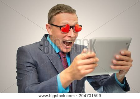 Online Dating. Fall in love. Womanizer man. Man in suit heart shape glasses and wide open mouth looking on tablet computer screen and admires of beautiful lady.