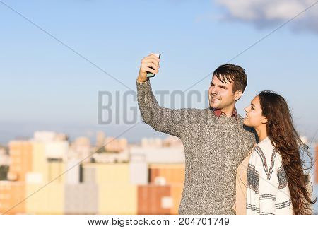 Young man and smiling pretty woman making selfie otdoors