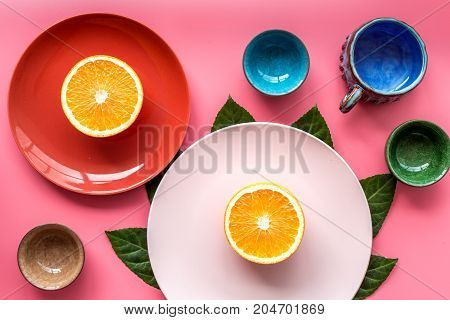 Colored cups and plates pattern decorated by exotic leaves and fruits on pink background top view.
