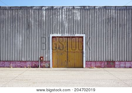 The sheet metal factory wall with the entrance door in the industrial park.The red door of the factory building