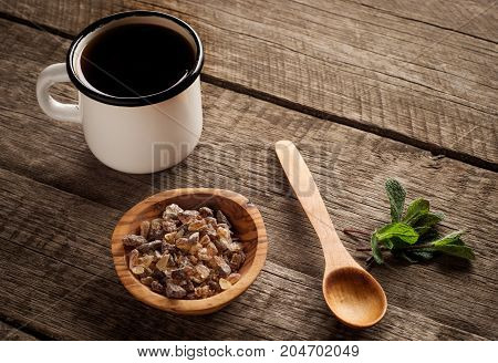old enamel cup of tea with brown sugar mint and wooden spoon on vintage wooden background.