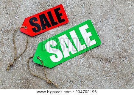 Colored sale labels on light stone background top view.