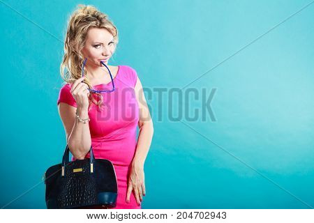 Beauty and fashion. Middle aged fashionable woman wearing pink vivid color dress holds handbag purse bag and eyeglasses studio shot on blue