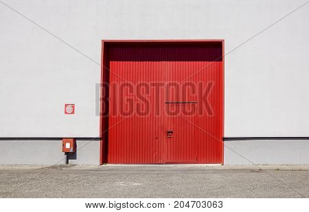 The sheet metal factory wall with the red entrance door in the industrial park.The red door of the factory building