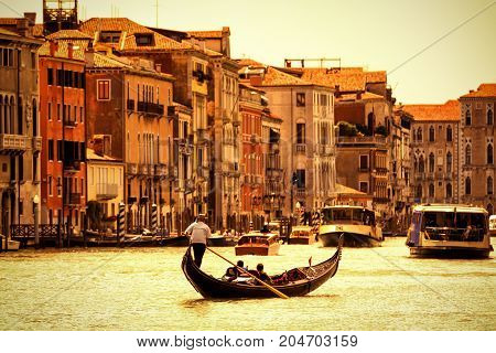 Gondola with tourists floats along the Grand Canal in Venice, Italy. Grand Canal is one of the major water-traffic corridors in Venice.