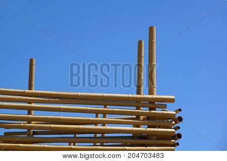Hanging Bamboo Canes Close Each Other, Blue Sky in background .