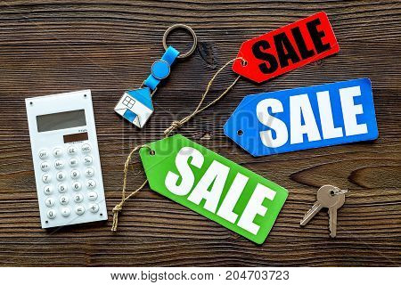 Count the benefits from the sale. Word sale on colored labels near calculator on wooden background top view.