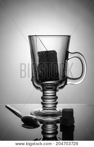 beautiful transparent glass with tea bag. Sugar and a spoon are lying on the table. Beautiful black and white picture. Unusual advertising still life. Morning tea.
