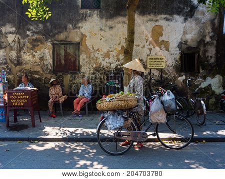Hoian, Vietnam - August 20, 2017: Unidentified woman walking with bike, at outdoor of Hoi an ancient town, in Vietnam.