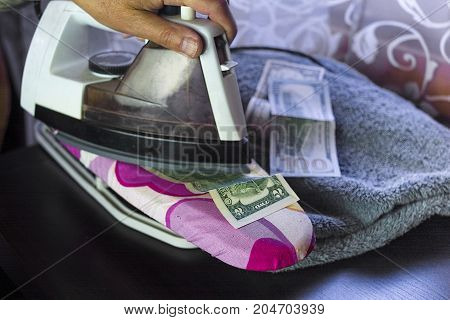 Male hand ironing a dollar bill on a table concept of money laundry and corruption