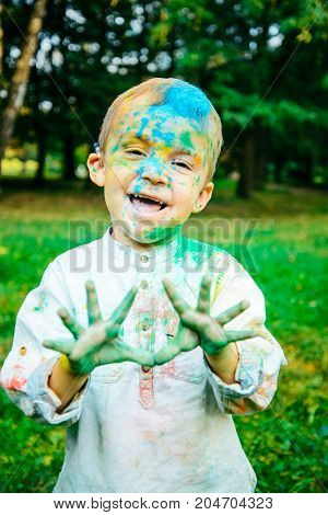 portrait of happy little kid all in holi paints