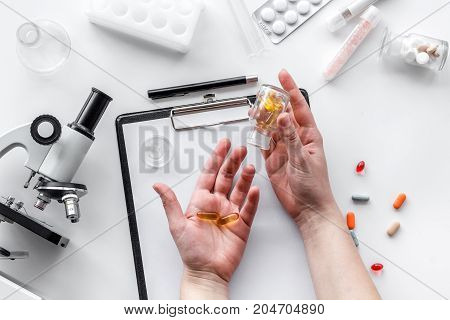 Do medcal tests. Hands hold pills near microscope on white background top view.