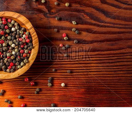 Peppercorns in a wooden bowl on a dark wooden background.