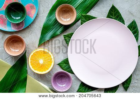 Empty plate mockup. Cups and plates near tropical leaves and fruits on grey background top view.