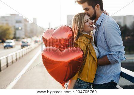 Beautiful couple in love cuddling while enjoying beautiful urban sunset together