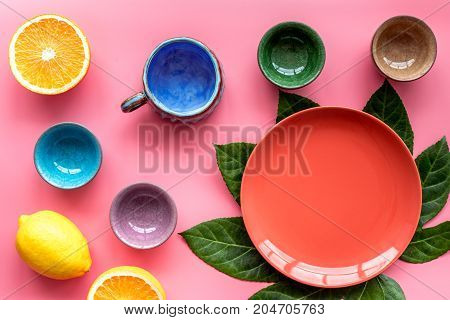 Empty plate mockup. Cups and plates near tropical leaves and fruits on pink background top view.
