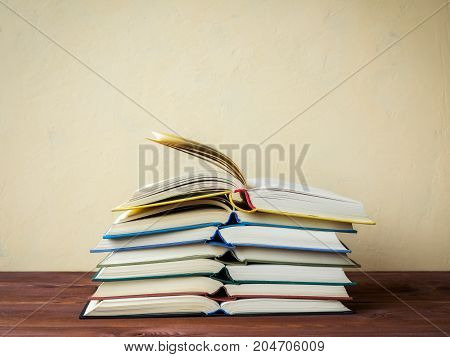 Pile of open books lying on the table