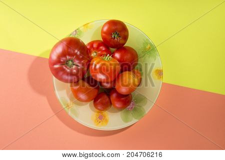 Abstract still life with tomatoes on a plate on a yellow-pink background