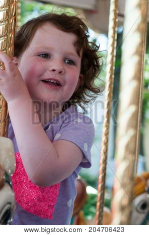 View of Young girl riding on fairground horse on carousel amusement ride at fairgrounds park outdoor