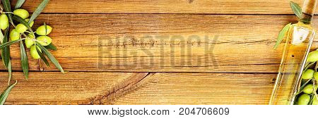 olive oil and branch with olives on old wooden surface