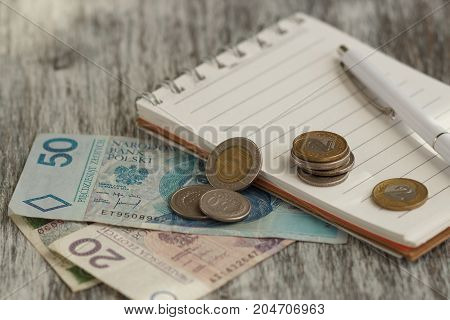 Polish Zloty, Notebook And Pen On The Wooden Background