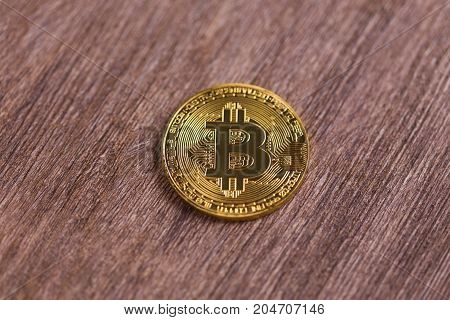 Golden bitcoin on wooden background. Crypto currency, virtual money, internet and economics concept.