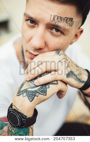 Portrait of young confident man covered with tattoos posing and looking at camera.