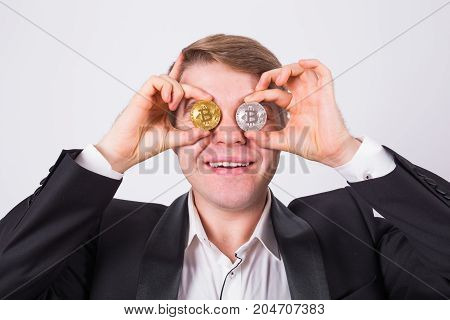 Crazy bitcoin lover with golden and silver coins by eyes, funny miner with coins