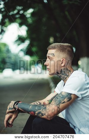 Young casual man with tattoos all over body in casual t-shirt posing at street looking away.