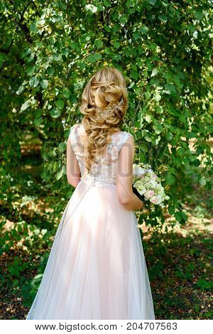 Beautiful Bride In Wedding Dress With Bridal Bouquet In The Park Outdoors, Back View. Blond Girl Wit