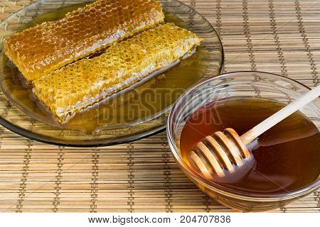 Honeycomb and honey in glass bowl with wooden honey dipper on natural matting