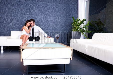 A young beautiful couple on the sofa, with a glass of wine, in the evening.