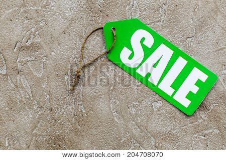 Green sale label on light stone background top view copyspace.