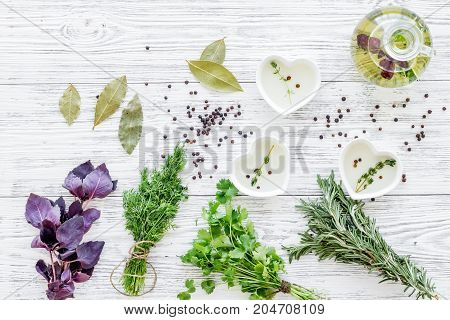 greenery with natural oil for home food cooking on light wooden kitchen table background top view