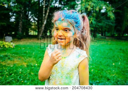 happy little girl portrait , all face in holi paints close up