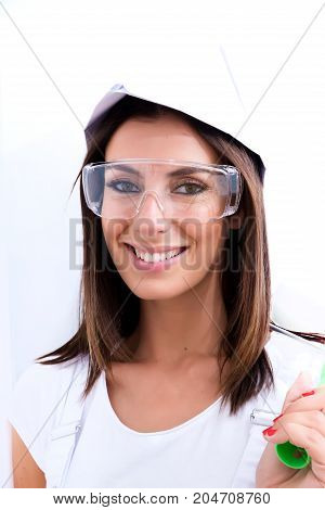 Beautiful young woman getting ready to paint her Apartment with safety glasses and a paper hat.