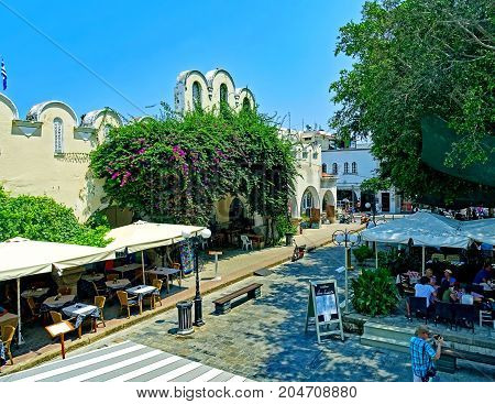 Kos, Greece - July 31, 2015: People enjoying a sunny summer day in outdoor restaurants at the market hall in the old town of Kos town on the island of Kos in Greece.