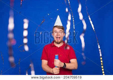 Young funny man with confetti. Holidays, carnival, christmas and new year party concept.