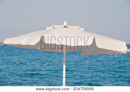 White textile beach umbrella on a background of blue sea on sunny day
