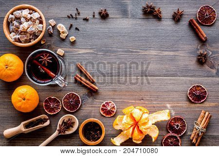 Hot mulled wine or grog cooking for new year celebration with oranges and spices ingredients on wooden table background flat lay mock-up