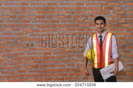 portrait of architect builder in front of brick wall with copy space