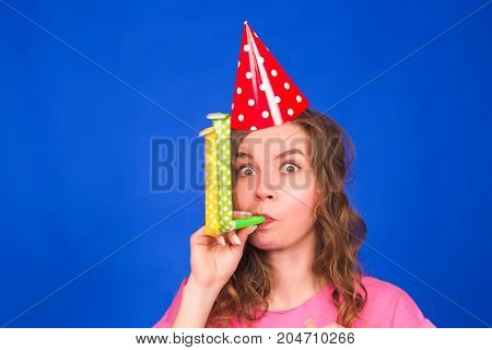 Young attractive funny woman with birthday hat and whistle on blue background. celebration and party.