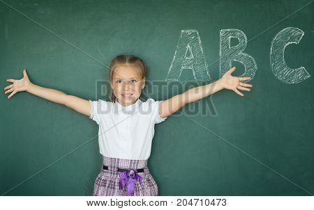 Portrait Of Caucasian Happy Child Girl With. School Chalkboard Or Blackboard Background. Education C