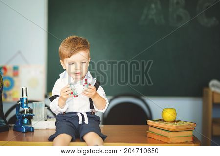 Cute Little Boy Sit On Desk And Smiling In Classroom On Chalkboard Background