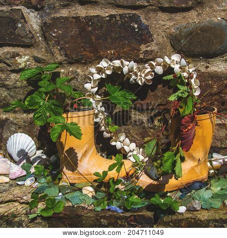 The original composition consists of children's boots sea shells and strawberries. Items are on the background of a stone wall. Element of street decor in the village of Clovelly. Devon. England