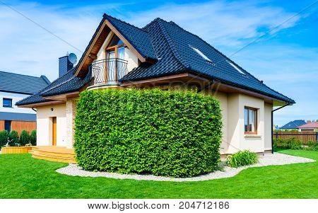 Single family house with lawn and hedge against blue sky